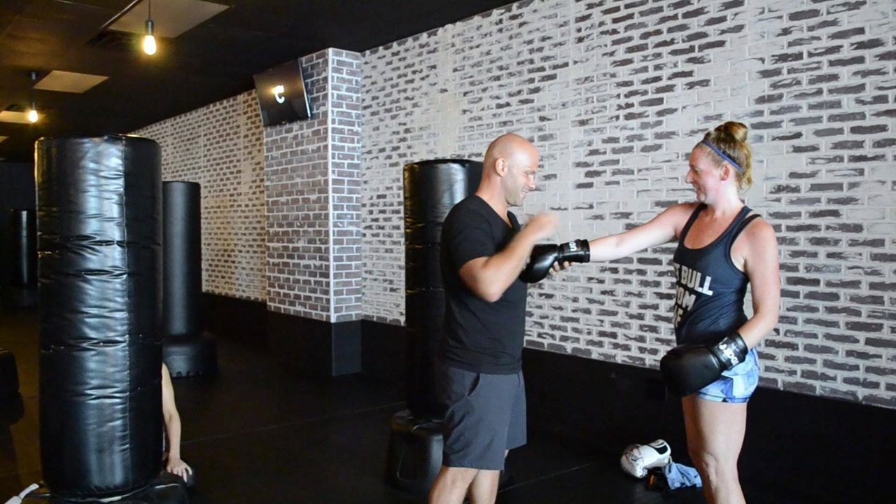 Instructor assisting a customer with her gloves at udar kickboxing class in long beach ny